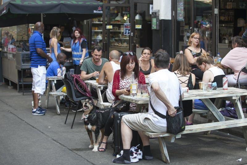 Das Mädchen mit einem Hund und einem Koffer, die in einem Straßencafé sitzen stockfotografie