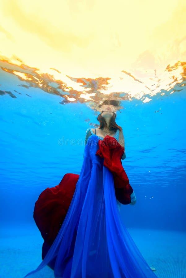 Das Mädchen mit einem roten und blauen Stoff in ihren Händen knallt oben von der Unterseite des Pools zur Oberfläche Schießen unt lizenzfreies stockbild