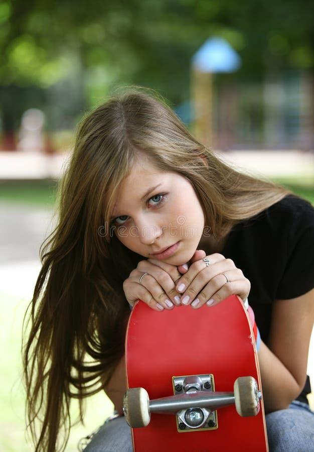 Das Mädchen mit einem Skateboard stockfoto