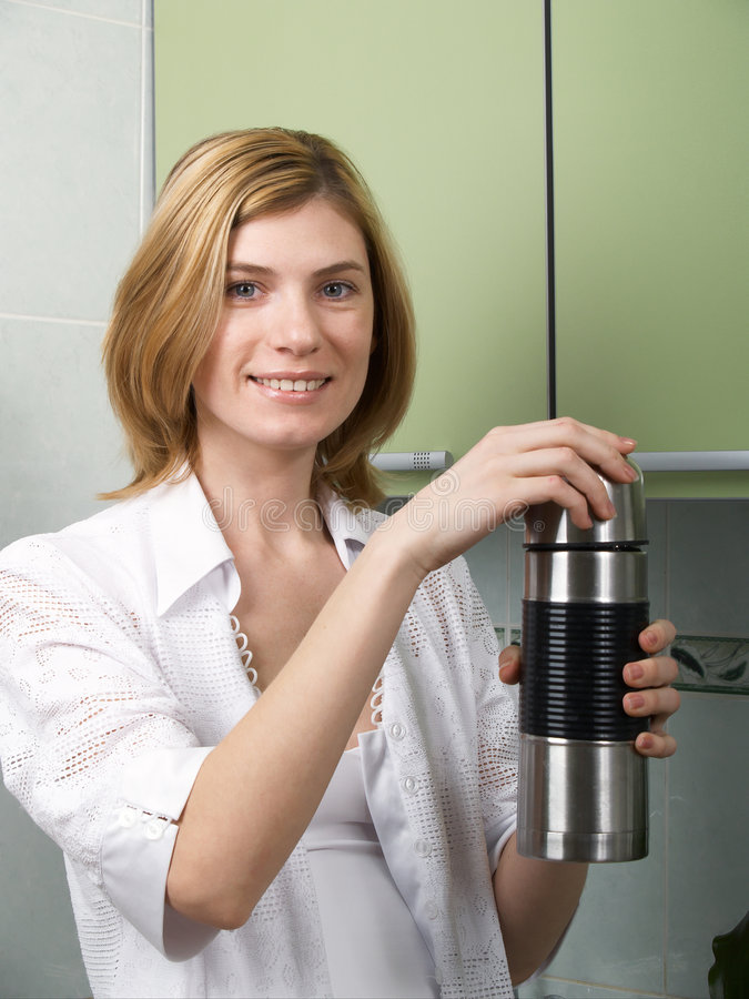 Das Mädchen mit einem Thermos in den Händen stockfoto
