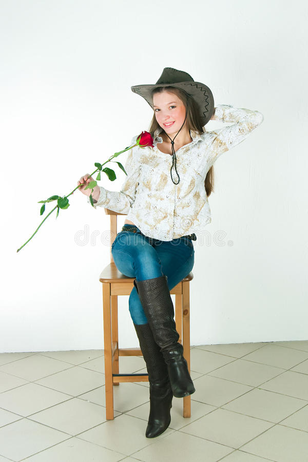 Das Mädchen mit einer Rose in einem Cowboyhut lizenzfreie stockfotos