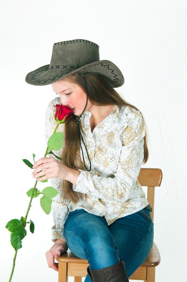 Das Mädchen mit einer Rose in einem Cowboyhut lizenzfreies stockbild