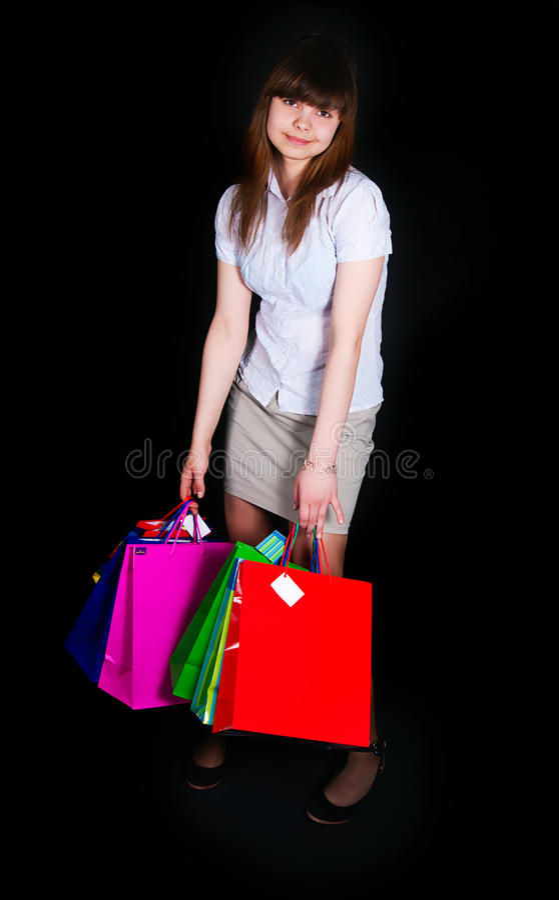 Das Mädchen mit mehrfarbigen Papierpaketen lizenzfreies stockfoto