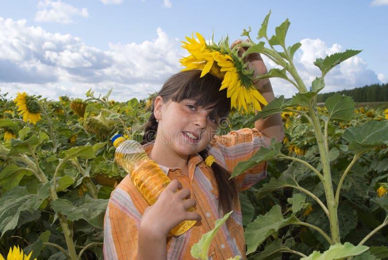 Das Mädchen mit Sonnenblume und Flasche Schmieröl lizenzfreies stockfoto