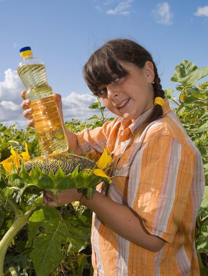 Das Mädchen mit Sonnenblume und Flasche Schmieröl stockbilder