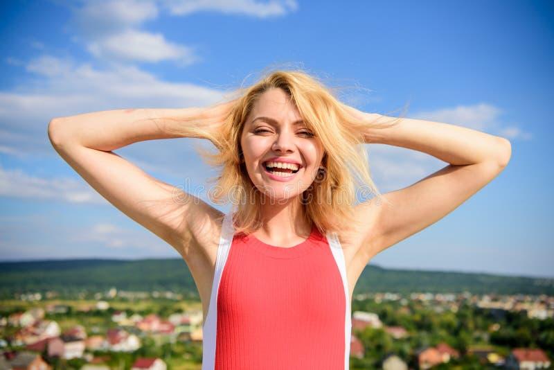 Das Mädchen, das mit warmem Sonnenlicht gefallen wird, schaut entspannten Hintergrund des blauen Himmels Blondes draußen sich ent stockbild