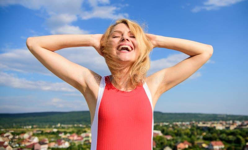 Das Mädchen, das mit warmem Sonnenlicht gefallen wird, schaut entspannten Hintergrund des blauen Himmels Mach's gut Hautachselhöh stockfoto