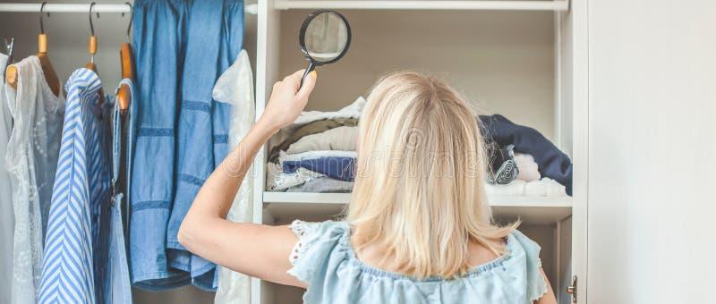 Das Mädchen nahe der Garderobe mit Kleidung schaut mit einer Lupe, die sie tragen sollte Schweres auserlesenes Konzept nichts zu  lizenzfreies stockfoto