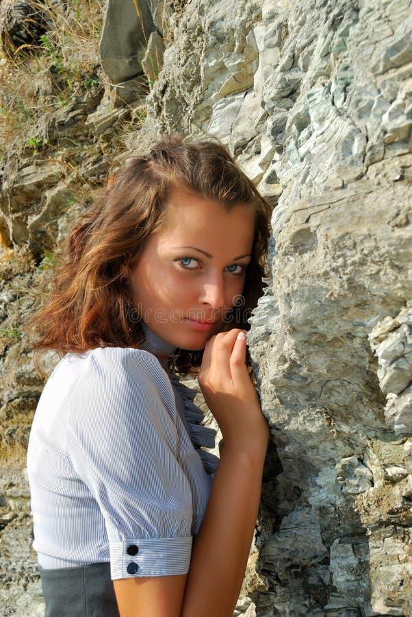 Das Mädchen nahe einem Felsen stockfotografie