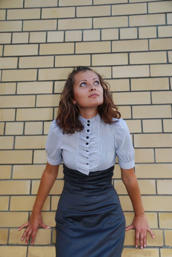 Das Mädchen nahe einer Backsteinmauer stockbild