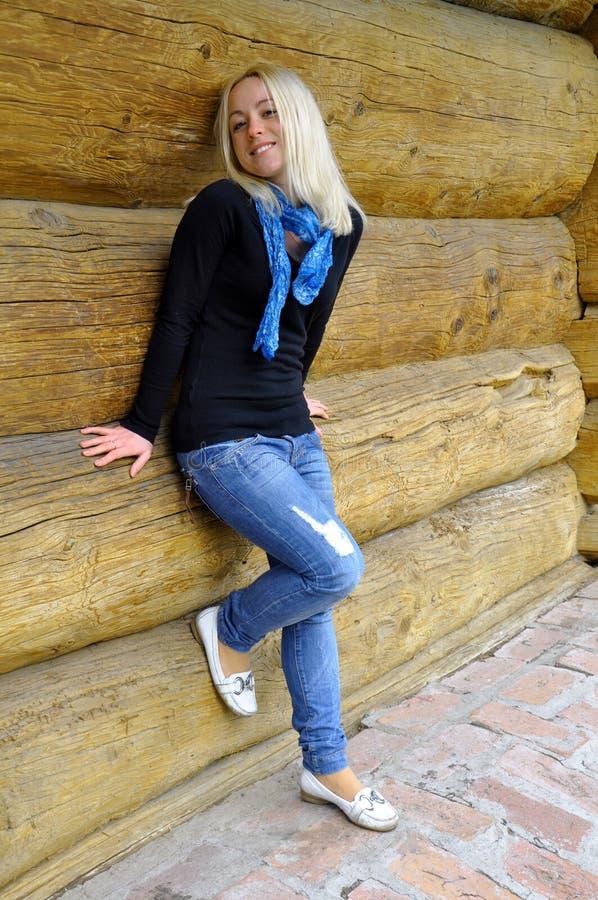 Das Mädchen nahe einer Protokollhütte lizenzfreie stockfotografie