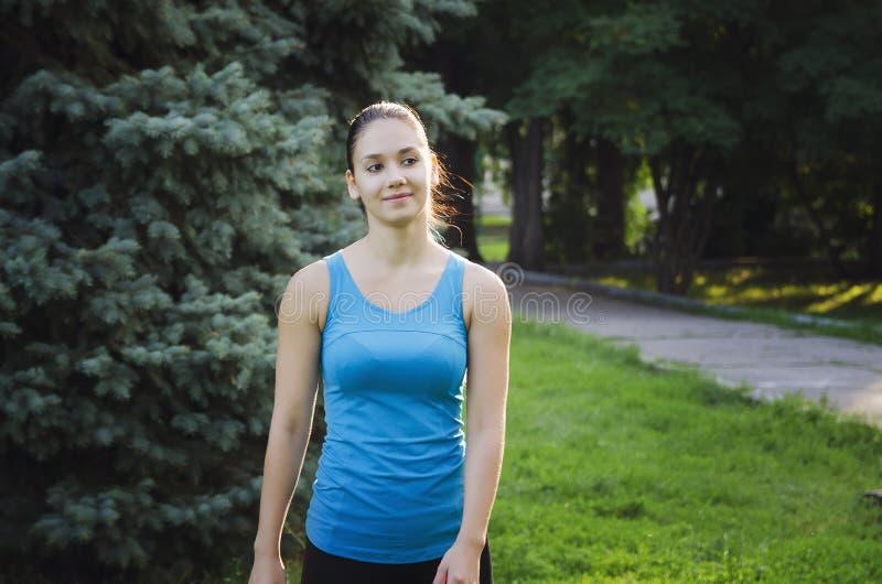 Das Mädchen nimmt an dem Sport teil, der in den Park läuft Training auf der Straße am Sommermorgen Gesunder Lebensstil des Konzep stockbild