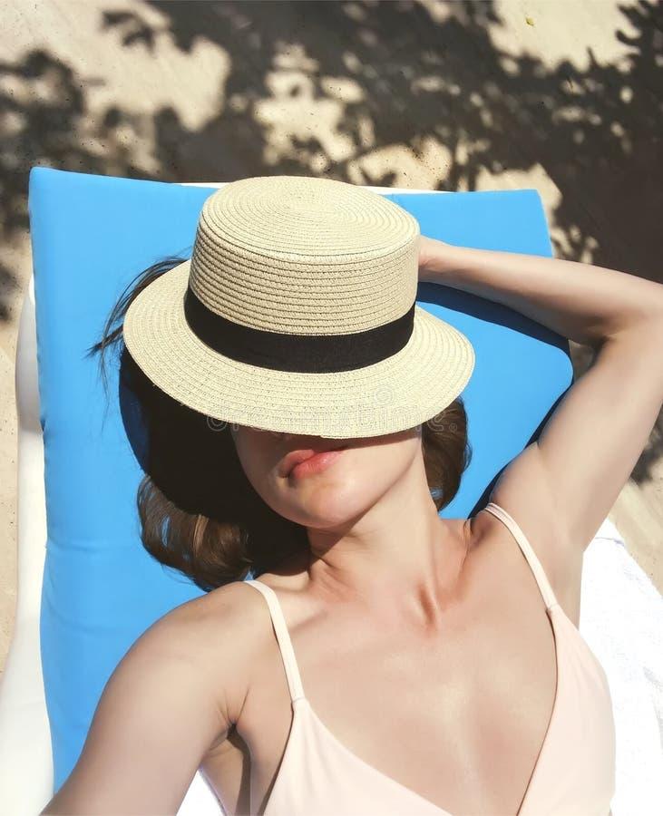 Das M?dchen nimmt in einem Klubsessel nahe dem Pool ein Sonnenbad und bedeckt ihr Gesicht mit einem Hut lizenzfreie stockbilder