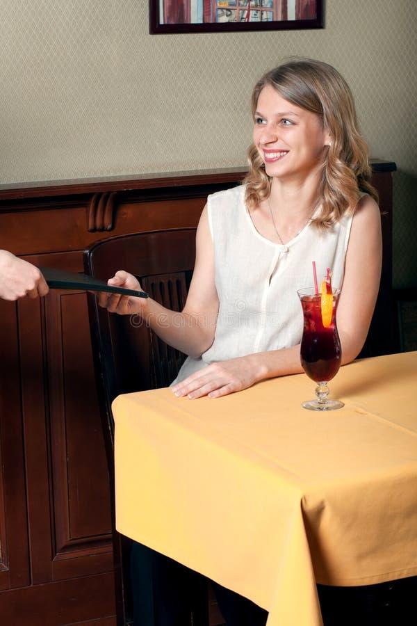 Das Mädchen nimmt ihr Handmenü im Café lizenzfreies stockbild