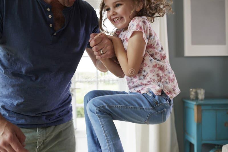 Das Mädchen, das oben springt und zu Hause dadï ¿ ½ s Hand, mittlerer Abschnitt hält stockfoto