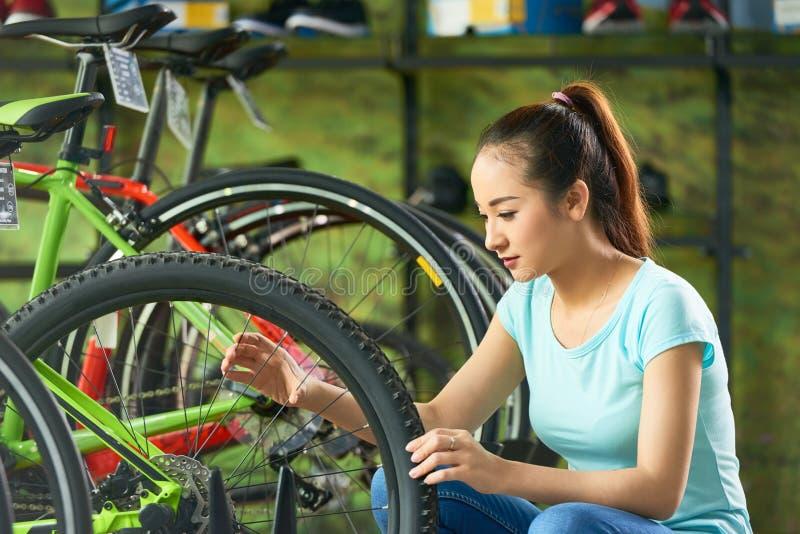 Das Mädchen, das Rad überprüft, sprach stockbild
