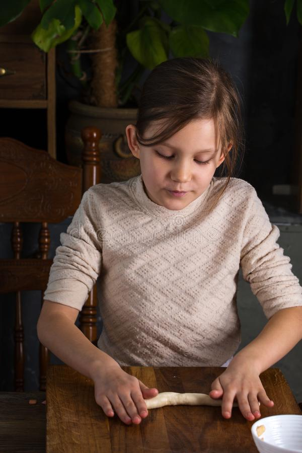 Das Mädchen rollt den Teig lizenzfreie stockfotos