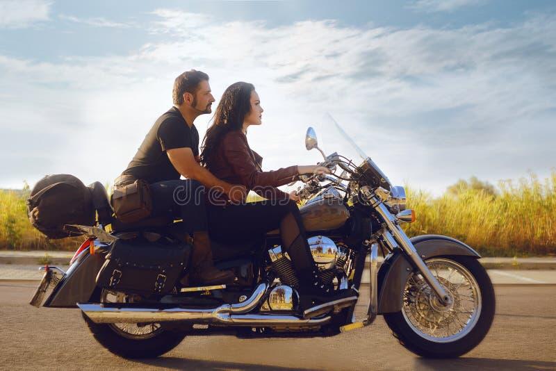 Das Mädchen rollt ihren Freund auf einem Motorrad Mädchen fährt ein Motorrad, der Kerl sitzt in der Rückseite stockfoto