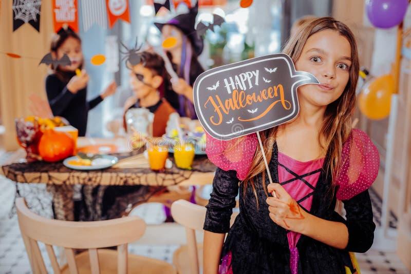 Das Mädchen, das rosa und schwarzes Halloween-Kleidergefühl trägt, überraschte durch die Partei lizenzfreie stockbilder