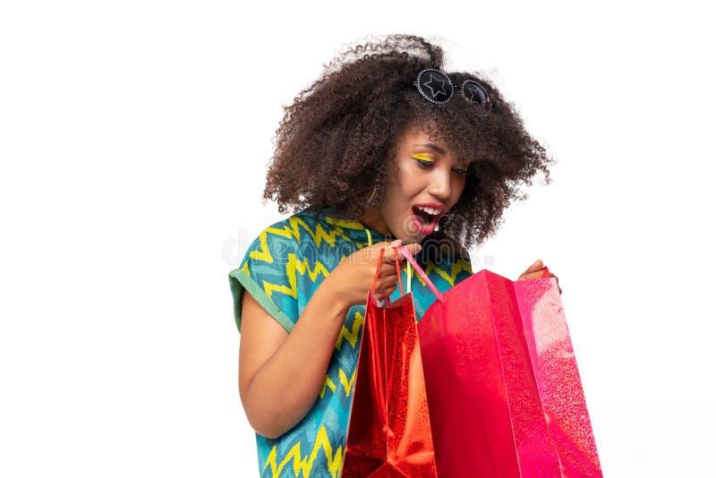 Das Mädchen schaut in den Einkaufstaschen lizenzfreie stockfotografie