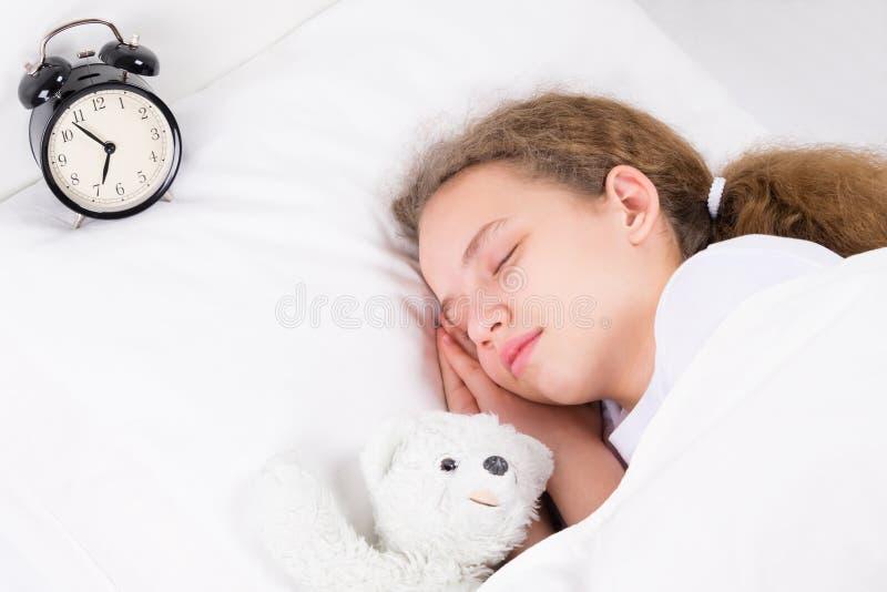 Das Mädchen schläft mit einem Wecker und umarmt lizenzfreie stockfotos