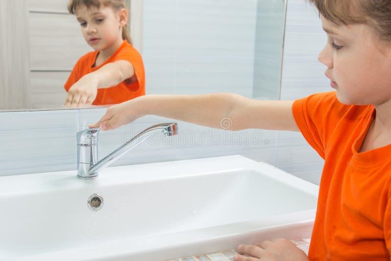 Das Mädchen schloss das Wasser vom Mischer, nachdem sie sich gewaschen hatte lizenzfreies stockbild