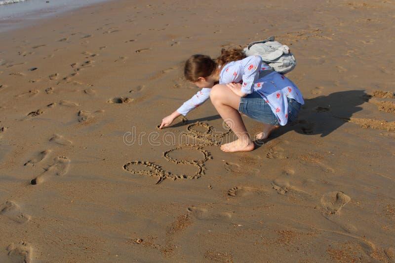 Das Mädchen schreibt das Wort 'Liebe 'und ein Symbol vom Herzen auf den Sand bei Sonnenuntergang Abdr?cke auf dem Meersand stockfotos