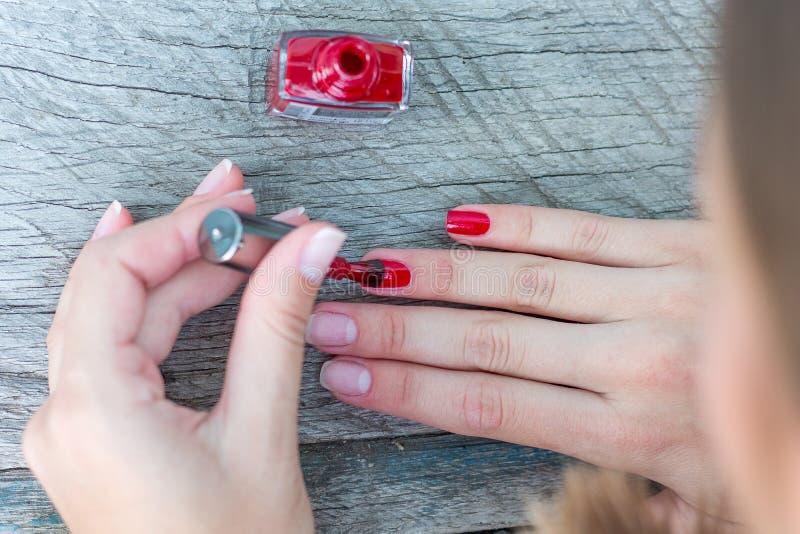 Das Mädchen setzt einen schwarzen Lack auf ihr nails_ lizenzfreies stockbild