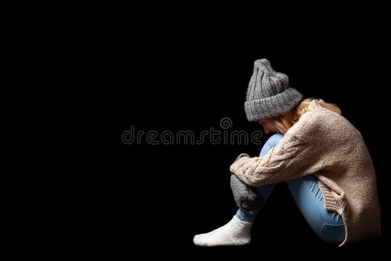 Das Mädchen sitzt allein auf dem Boden auf einem schwarzen Hintergrund der Leere, umarmt ihre Beine mit ihren Händen und lässt ih stockfotografie