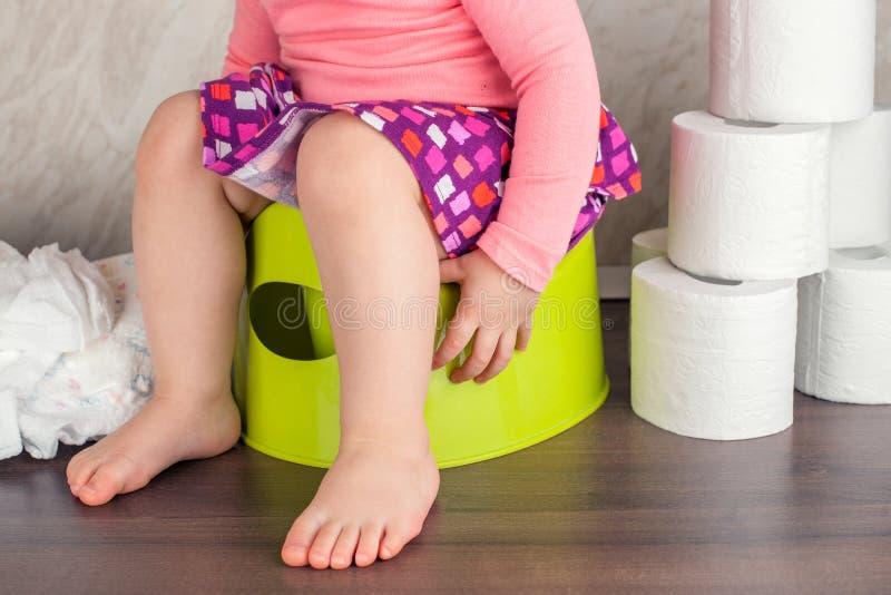 Das Mädchen sitzt auf einem grünen Topf und lernt grundlegende Hygiene stockfoto