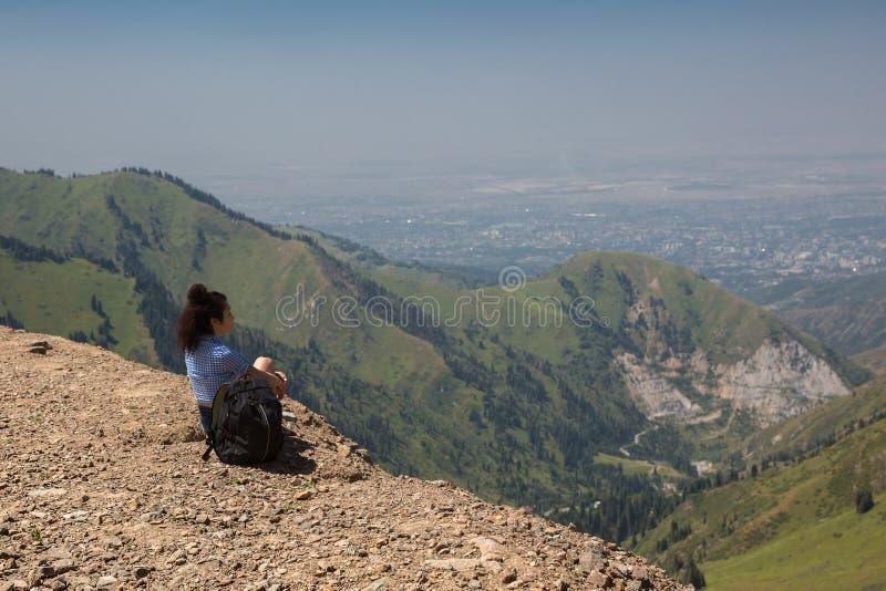 Das M?dchen sitzt auf einem hohen Berg und Blicken an der Stadt lizenzfreie stockfotos
