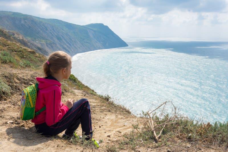 Das Mädchen sitzt auf hoher Bank und betrachtet das Meer lizenzfreies stockfoto