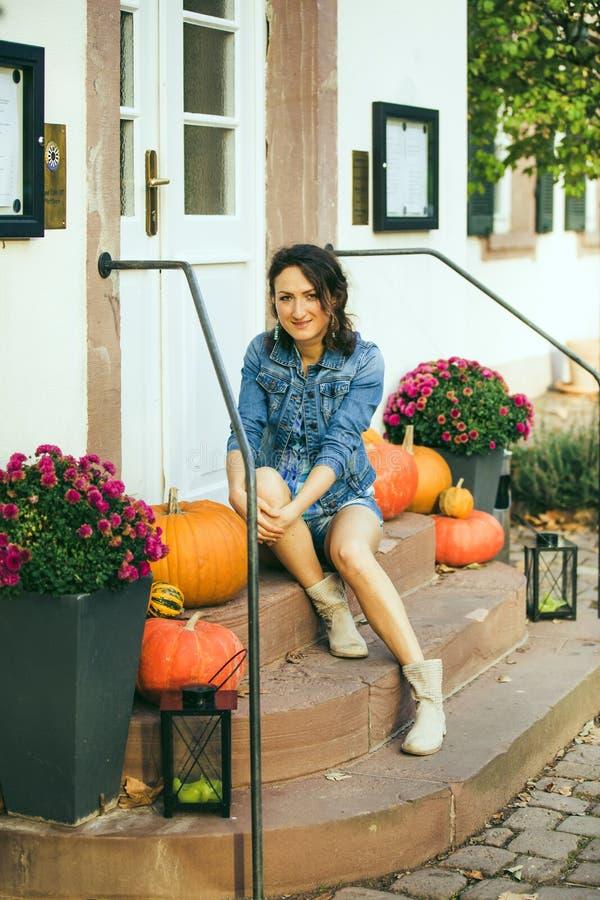 Das Mädchen sitzt auf Schritten mit Kürbisen auf Halloween lizenzfreie stockbilder