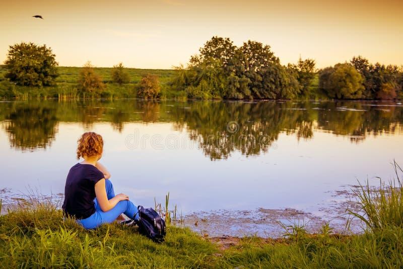 Das Mädchen sitzt durch den Fluss am Abend und am Bewundern national stockfotos