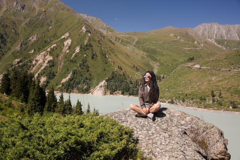 Das Mädchen sitzt in einem Lotussitz auf einem großen Stein nahe dem Fluss lizenzfreie stockbilder