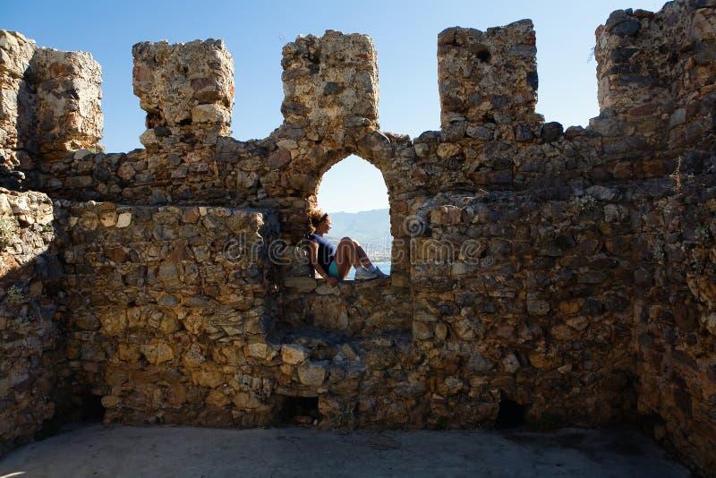 Das Mädchen sitzt im Schlupfloch der Festungswand lizenzfreies stockbild