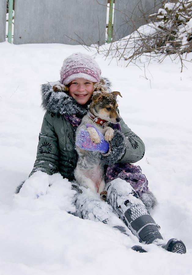 Das Mädchen sitzt im Schnee mit ihrem geliebten dog_ lizenzfreies stockbild