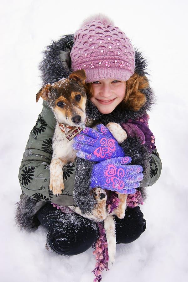 Das Mädchen sitzt im Schnee und hält in den Händen von ihr geliebt lizenzfreie stockfotos
