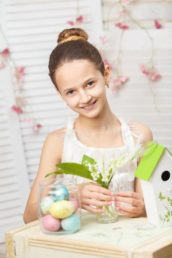 Das Mädchen sitzt am Tisch und hält Blumen und gemalte Eier lizenzfreie stockfotografie