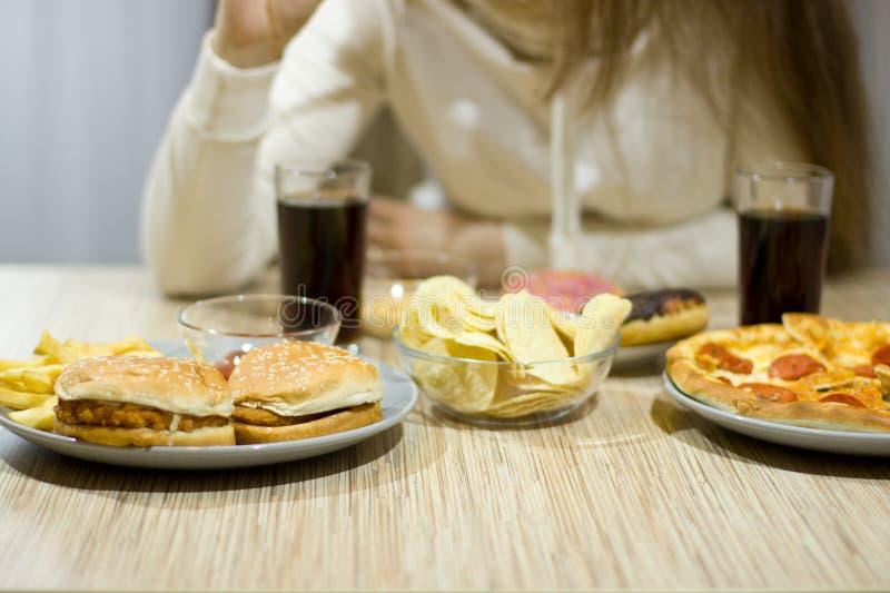 Das Mädchen sitzt am Tisch und isst Schnellimbiß stockfotografie