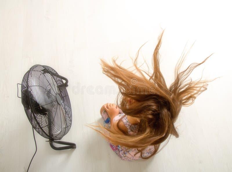 Das Mädchen sitzt vor dem Fan lizenzfreies stockfoto