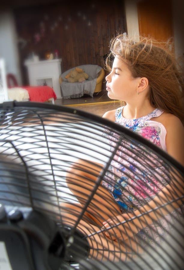 Das Mädchen sitzt vor dem Fan lizenzfreie stockfotografie