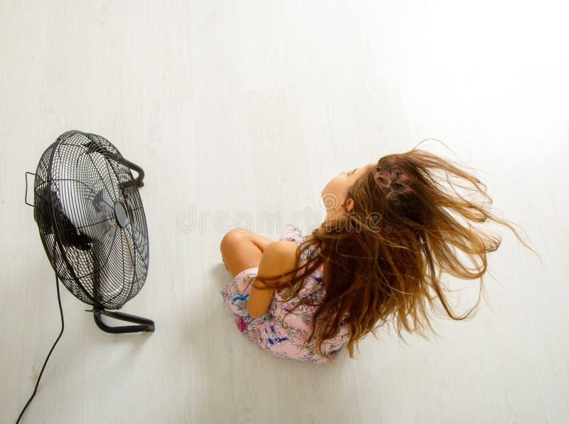 Das Mädchen sitzt vor dem Fan stockfoto