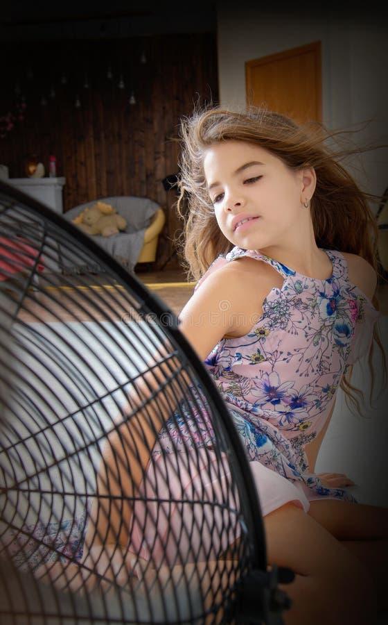 Das Mädchen sitzt vor dem Fan stockfotos