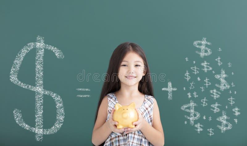 das Mädchen, das Sparschwein hält und speichern Geldkonzept stockbild