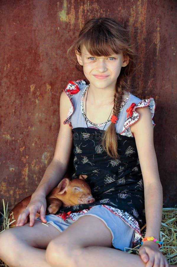 Das Mädchen spielt mit roten neugeborenen Schweinen der Duroczucht Das Konzept von mitfühlendem und von Interessieren für Tiere lizenzfreies stockbild