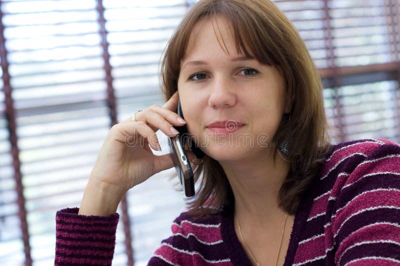 Das Mädchen spricht durch einen Handy stockfotos