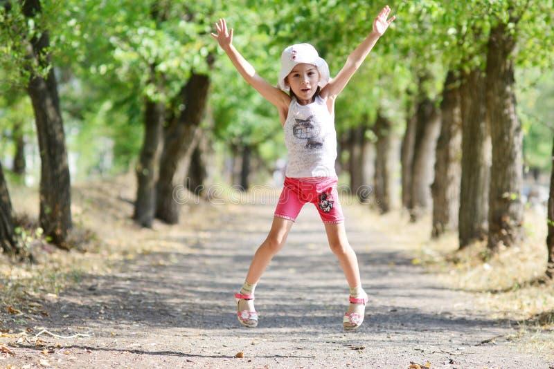 Das Mädchen springend auf die Parkgasse stockfotos