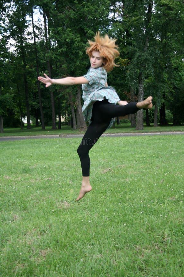 Das Mädchen springend auf Gras lizenzfreie stockfotos