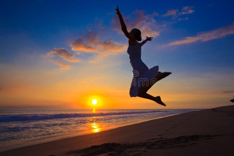 Das Mädchen springend in den Sonnenuntergang lizenzfreies stockfoto